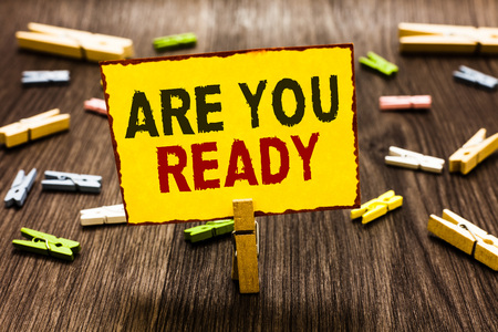 Handwriting text writing Are You Ready. Concept meaning Alertness Preparedness Urgency Game Start Hurry Wide awake Clothespin holding yellow paper note several clothespins wooden floor