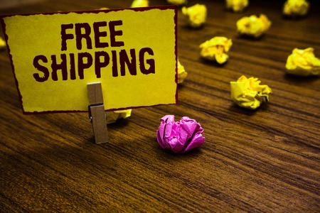 Writing note showing Free Shipping. Business photo showcasing Freight Cargo Consignment Lading Payload Dispatch Cartage Clothespin holding yellow paper note crumpled papers several tries Stock Photo
