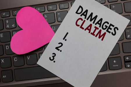 Handwriting text Damages Claim. Concept meaning Demand Compensation Litigate Insurance File Suit Paper Romantic lovely message Heart Keyboard Type computer Good feelings