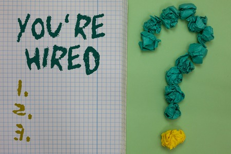 Text sign showing You re are Hired. Conceptual photo New Job Employed Newbie Enlisted Accepted Recruited Notebook paper crumpled papers forming question mark green background