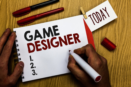 Handwriting text writing Game Designer. Concept meaning Campaigner Pixel Scripting Programmers Consoles 3D Graphics Man holding marker notebook clothespin reminder wooden table cup coffee