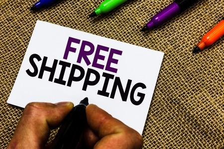 Writing note showing Free Shipping. Business photo showcasing Freight Cargo Consignment Lading Payload Dispatch Cartage Man hand holding marker white paper communicating idea Jute background