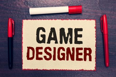 Writing note showing Game Designer. Business photo showcasing Campaigner Pixel Scripting Programmers Consoles 3D Graphics Open notebook page markers communicating ideas with wooden background Banco de Imagens