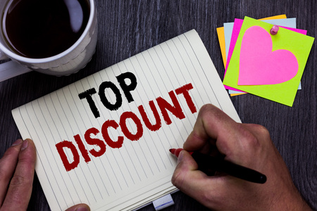 Conceptual hand writing showing Top Discount. Business photo text Best Price Guaranteed Hot Items Crazy Sale Promotions Man holding marker giving ideas wooden table cup coffee hearts