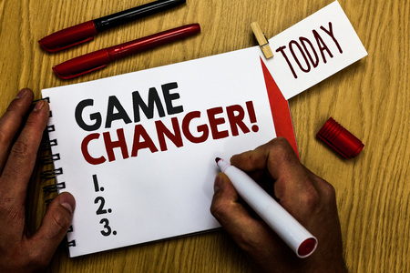 Handwriting text writing Game Changer. Concept meaning Sports Data Scorekeeper Gamestreams Live Scores Team Admins Man holding marker notebook clothespin reminder wooden table cup coffee