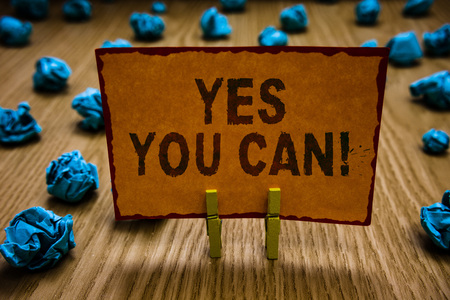 Conceptual hand writing showing Yes You Can. Business photo text Positivity Encouragement Persuade Dare Confidence Uphold Clothespins holding orange paper note crumpled papers mistake Banco de Imagens