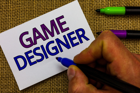 Text sign showing Game Designer. Conceptual photo Campaigner Pixel Scripting Programmers Consoles 3D Graphics Man hand holding marker white paper communicating ideas Jute background