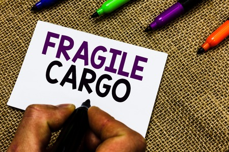 Writing note showing Fragile Cargo. Business photo showcasing Breakable Handle with Care Bubble Wrap Glass Hazardous Goods Man hand holding marker white paper communicating idea Jute background
