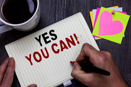 Conceptual hand writing showing Yes You Can. Business photo text Positivity Encouragement Persuade Dare Confidence Uphold Man holding marker giving ideas wooden table cup coffee hearts Banco de Imagens