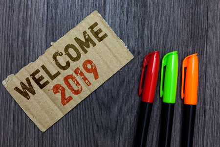 Word writing text Welcome 2019. Business concept for New Year Celebration Motivation to Start Cheers Congratulations Paperboard Important reminder Communicate ideas Markers Wooden background