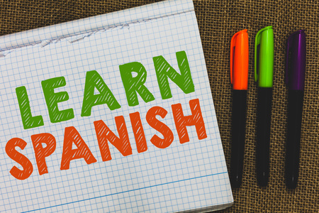 Conceptual hand writing showing Learn Spanish. Business photo text Translation Language in Spain Vocabulary Dialect Speech Open notebook jute background colorful markers Expressing ideas Stock Photo