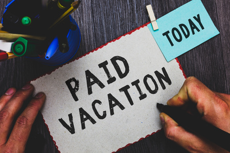 Conceptual hand writing showing Paid Vacation. Business photo text Sabbatical Weekend Off Holiday Time Off Benefits Man holding marker paper clothespin reminder cup marker wood table Foto de archivo