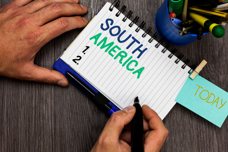 Conceptual hand writing showing South America. Business photo showcasing Continent in Western Hemisphere Latinos known for Carnivals Man holding marker notebook reminder cup markers wood table Banque d'images