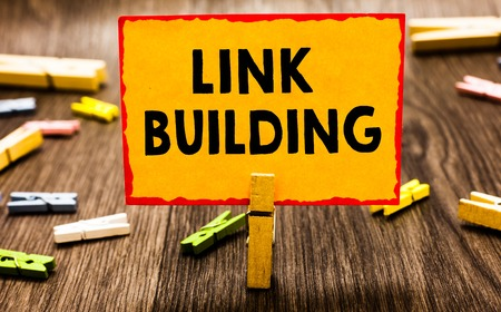 Conceptual hand writing showing Link Building. Business photo showcasing SEO Term Exchange Links Acquire Hyperlinks Indexed Clothespin holding orange paper note clothespin wooden floor