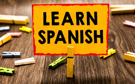 Conceptual hand writing showing Learn Spanish. Business photo showcasing Translation Language in Spain Vocabulary Dialect Speech Clothespin holding orange paper note clothespin wooden floor