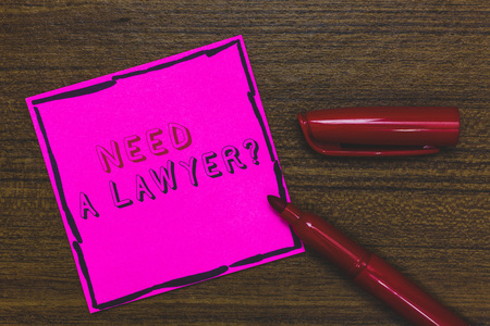 Handwriting text Need A Lawyer question. Concept meaning Legal problem Looking for help from an attorney Pink Paper Important reminder Communicate ideas Marker Wooden background