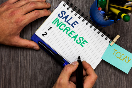Conceptual hand writing showing Sale Increase. Business photo showcasing Average Sales Volume has Grown Boost Income from Leads Man holding marker notebook reminder cup markers wood table