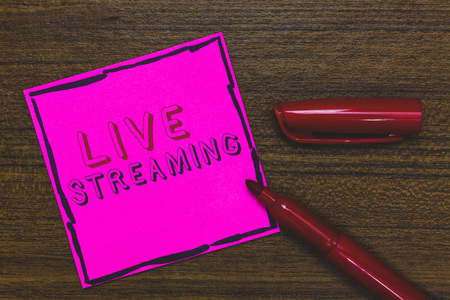 Handwriting text Live Streaming. Concept meaning Transmit live video coverage of an event over the Internet Pink Paper Important reminder Communicate ideas Marker Wooden background