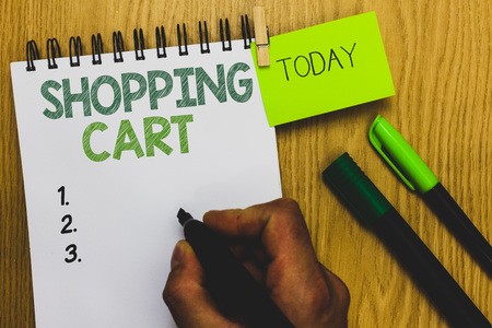 Word writing text Shopping Cart. Business concept for Case Trolley Carrying Groceries and Merchandise Man holding marker notebook clothespin reminder wooden table cup coffee 写真素材