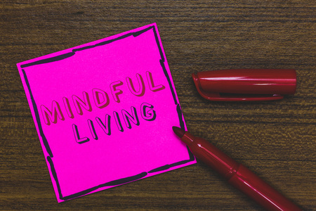 Handwriting text Mindful Living. Concept meaning Fully aware and engaged on something Conscious and Sensible Pink Paper Important reminder Communicate ideas Marker Wooden background