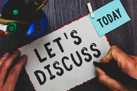 Conceptual hand writing showing Let s is Discuss. Business photo text Permit to Talk Open Up Go Over a Topic Chat Sharing Man holding marker paper clothespin reminder cup marker wood table