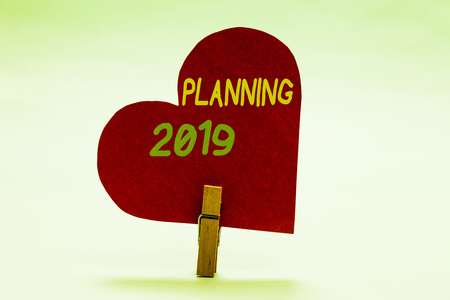 Writing note showing Planning 2019. Business photo showcasing Begin with end in the Mind Positioning Long term Objectives Clothespin holding red paper heart important romantic message ideas Banco de Imagens