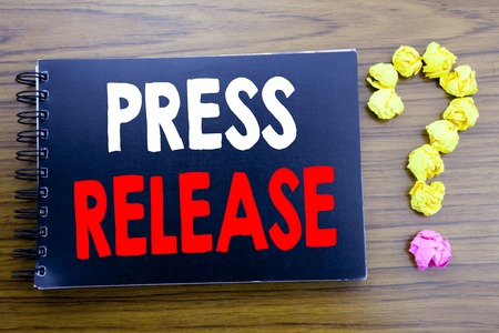Handwritten text showing Press Release. Business concept writing for Statement Announcement Message Written on notepad paper, wooden background in office view with question mark on the end.
