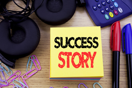 Word, writing Success Story. Business concept for Inspiration Motivation written on sticky note paper on wooden background. With calculator and pen marker and headphones