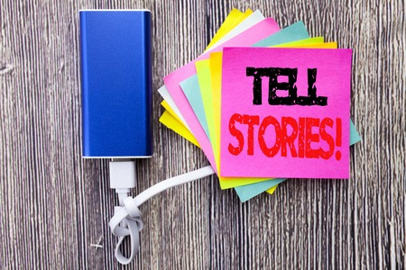 Tell Stories. Business concept for Storytelling Telling Story written on sticky note with space on old wood wooden background with power bank Reklamní fotografie
