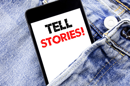 Hand writing text caption inspiration showing Tell Stories. Business concept for Storytelling Telling Story Written phone mobile phone, cellphone placed in man front jeans pocket.