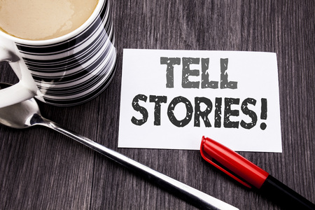 Conceptual hand writing text caption showing Tell Stories. Business concept for Storytelling Telling Story written on sticky note paper on wooden wood background. With coffee and marker