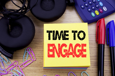Word, writing Time To Engage. Business concept for Engagement Involvement written on sticky note paper on wooden background. With calculator and pen marker and headphones