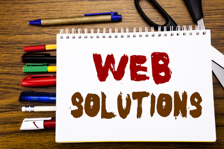 Word, writing Web Solutions. Business concept for Internet Design Plan Written on notebook, wooden background office equipment like pens scissors colourful marker