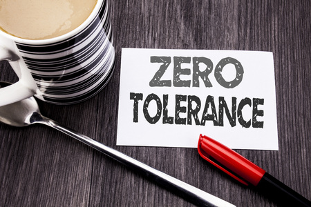 Conceptual hand writing text caption showing Zero Tolerance. Business concept for Policy For Punishment written on sticky note paper on wooden wood background. With coffee and marker Stock Photo