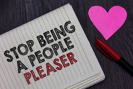 Writing note showing Stop Being A People Pleaser. Business photo showcasing Do what you like not things other people want Strikethrough words on notepad love heart pen on blackish woody desk Reklamní fotografie