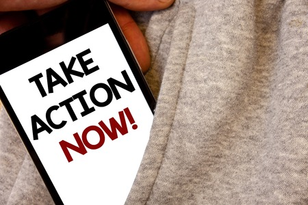 Text sign showing Take Action Now Motivational Call. Conceptual photo Urgent Move Start Promptly Immediate Begin Words written black Phone white Screen Hand holding pocket white tracksuit