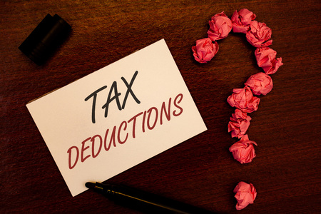 Text sign showing Tax Deductions. Conceptual photo Reduction on taxes Investment Savings Money Returns Text white paper note black marker open cap pink crumbled paper question Stock Photo