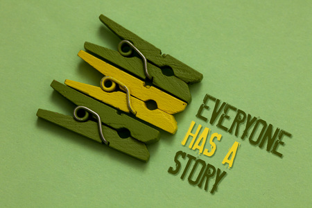 Handwriting text writing Everyone Has A Story. Concept meaning Background storytelling telling your memories tales Olive ground laid on paperclip in front some text of olive and yellow color