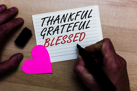 Handwriting text writing Thankful Grateful Blessed. Concept meaning Appreciation gratitude good mood attitude Written on notepad hand hold marker with love heart wooden background