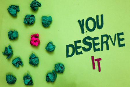 Writing note showing You Deserve It. Business photo showcasing Reward for something well done Deserve Recognition award Olive color floor scattered some green lump mid pink lob near words