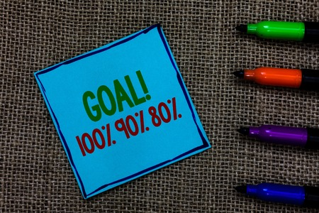 Writing note showing Goal 100 90 80. Business photo showcasing Percentage of your objectives fulfilment success level Blue paper on written letters besides color pens on black sack Stock Photo
