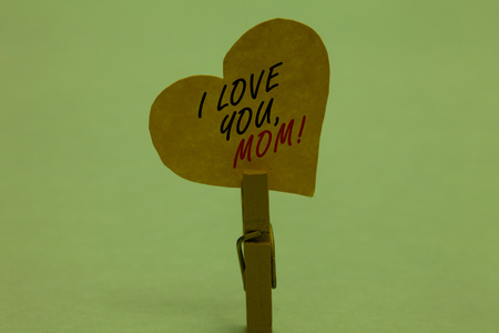 Handwriting text I Love You, Mom. Concept meaning Loving message emotional feelings affection warm declaration Celadon color background paper clip hold love heart for loving with words Stock Photo