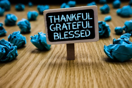 Word writing text Thankful Grateful Blessed. Business concept for Appreciation gratitude good mood attitude Paperclip hold black paperboard with text blue paper lobs on wooden floor Stock Photo
