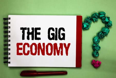 Writing note showing The Gig Economy. Business photo showcasing Market of Short-term contracts freelance work temporary Celadon color background red sided notepad letters green query mark Reklamní fotografie