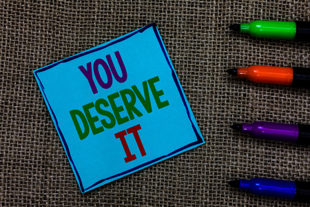 Writing note showing You Deserve It. Business photo showcasing Reward for something well done Deserve Recognition award Blue paper on written letters besides color pens on black sack
