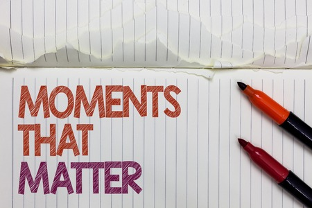 Text sign showing Moments That Matter. Conceptual photo Meaningful positive happy memorable important times White torn page written some letters beside laid two red marker Stock Photo