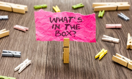 Conceptual hand writing showing What s is In The Box question. Business photo showcasing Curiosity Opening a gift Surprise package Paperclip hold pink note with texts many clips wooden floor Stock fotó