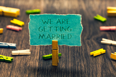 Conceptual hand writing showing We Are Getting Married. Business photo showcasing Engagement Wedding preparation Loving couple Paperclip retain blue cardboard blurry woody desk paper clip Foto de archivo