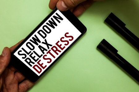Text sign showing Slow Down Relax De Stress. Conceptual photo Have a break reduce stress levels rest calm Mans hand hold phone with black and red words near two black marker Stok Fotoğraf