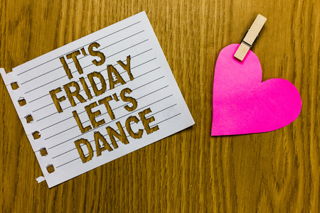 Conceptual hand writing showing It s is Friday Let s is Dance. Business photo showcasing Celebrate starting the weekend Go party Disco Music Yellow woody deck word white page paper clip grip heart Banco de Imagens